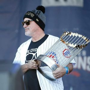 Joe Madden holding Chicago Cubs World Series trophy